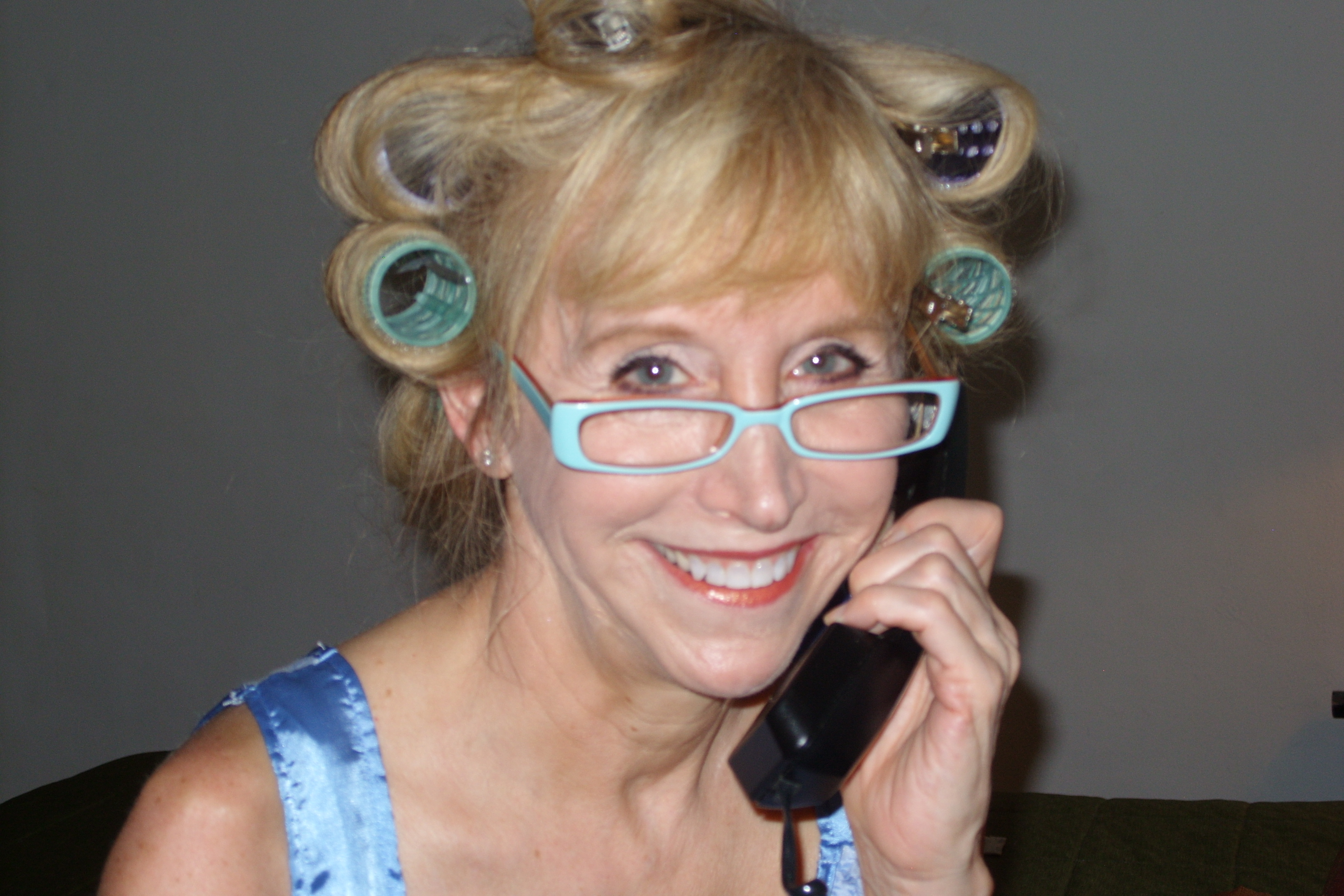 Blonde woman in hair curlers on telephone