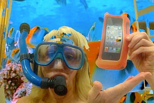 Woman in fake aquarium holding iPhone in LifeProof case