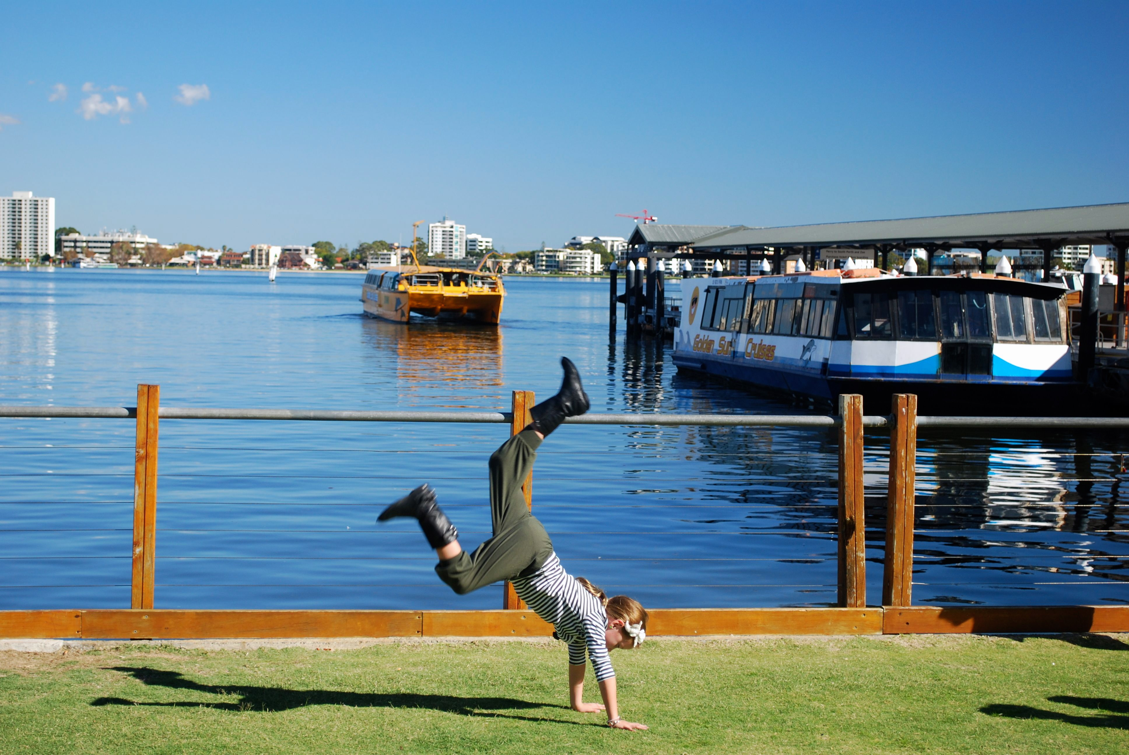 Child doing handstand near Swan River in Perth