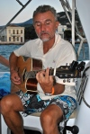 Man playing guitar on sailboat