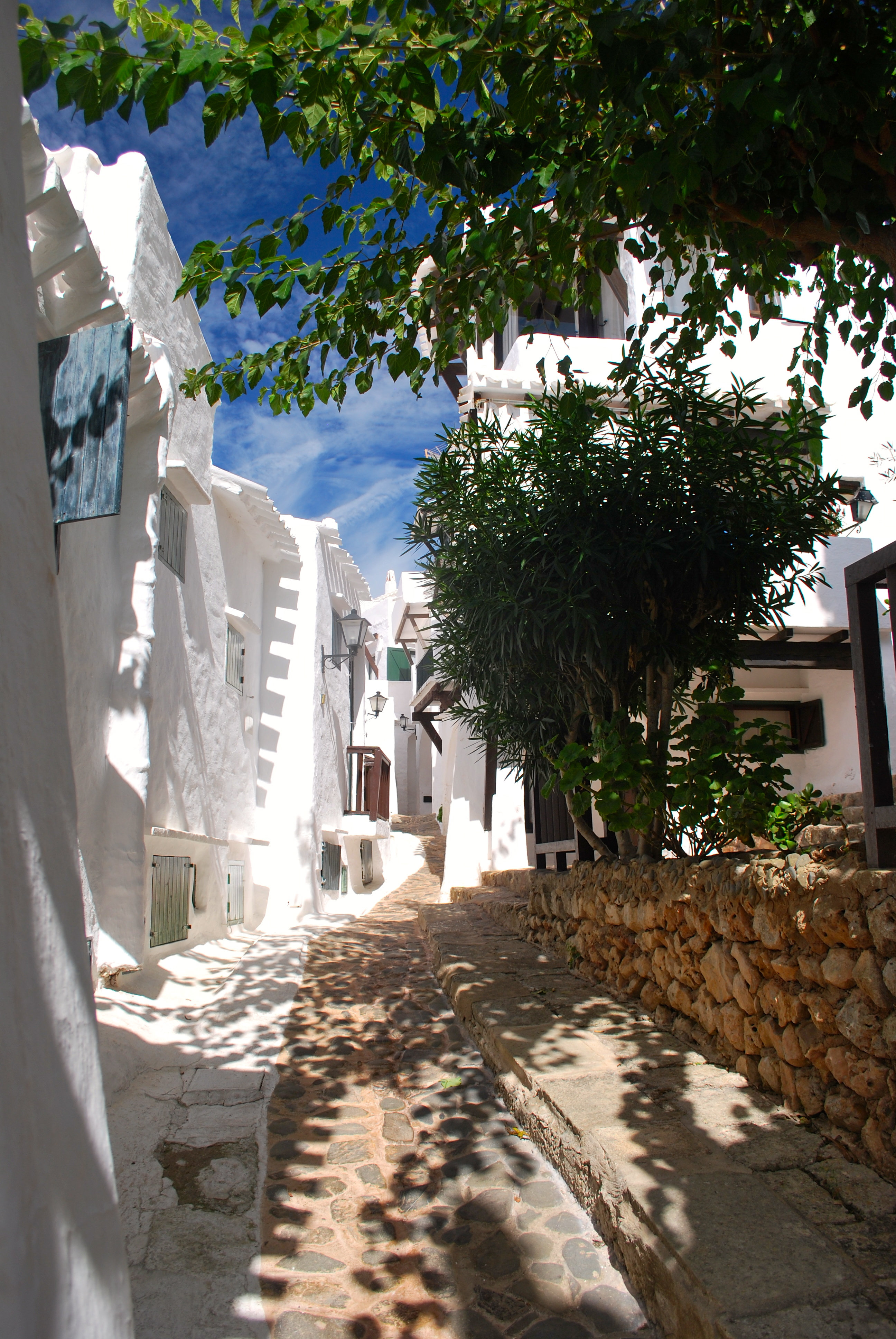 Sun dappled  pedestrian-only street in Binibecca Vell, Menorca