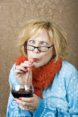 Crazy looking woman drinking wine through a straw
