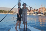 a blonde and a brunette woman standing on a sailboat in Greece