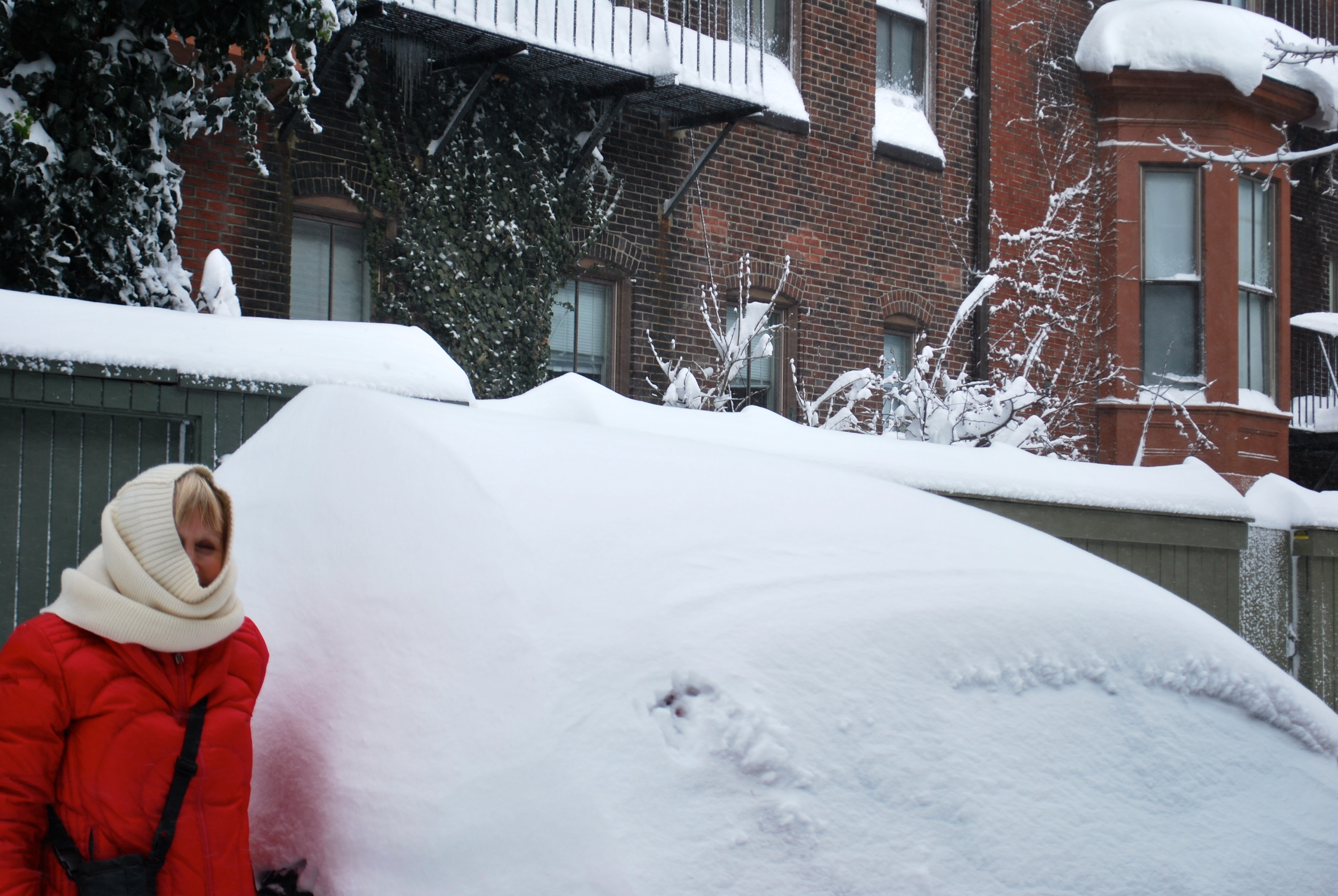 Blonde woman at car with snow on it in Boston