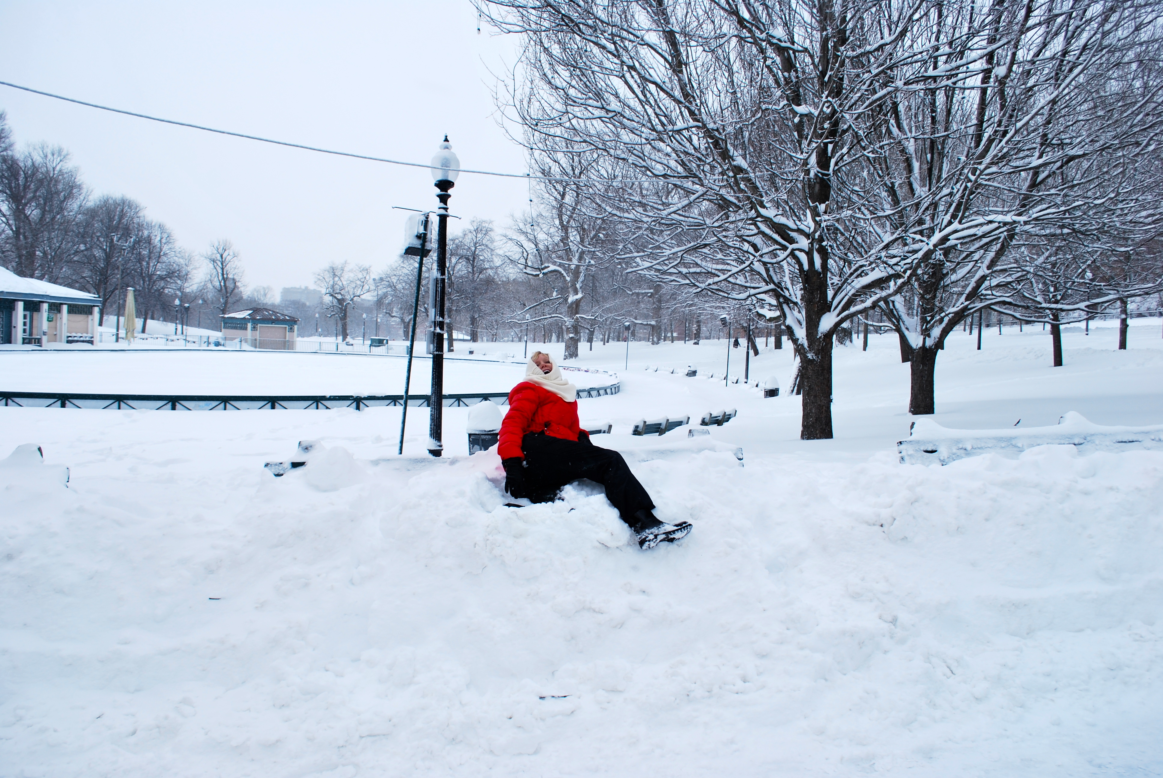 Blonde attempting to sit on park bench covered in snow