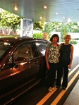 Two women standing beside a Bentley at the airport in Singapore