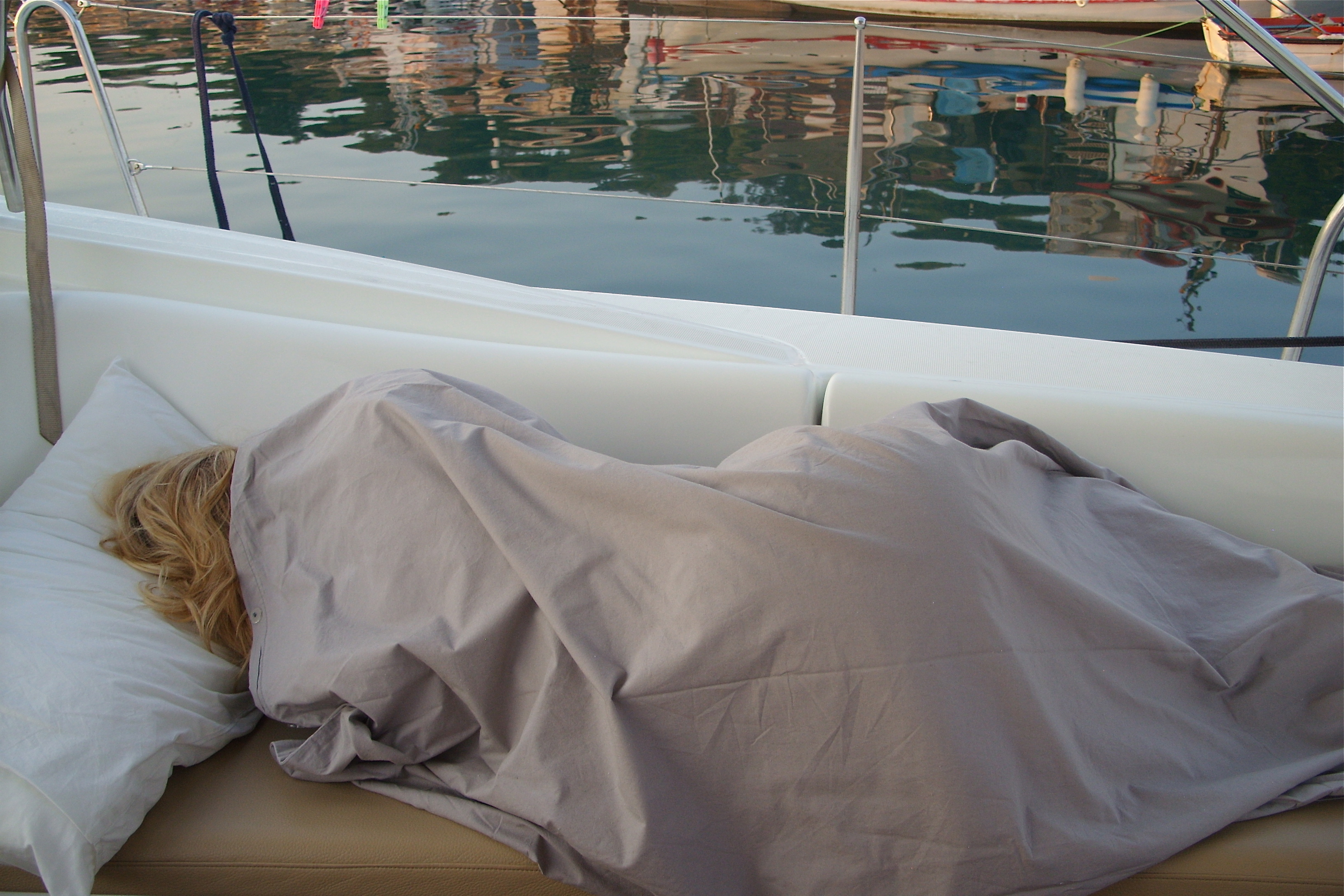 Blonde woman sleeping under a sheet on a boat