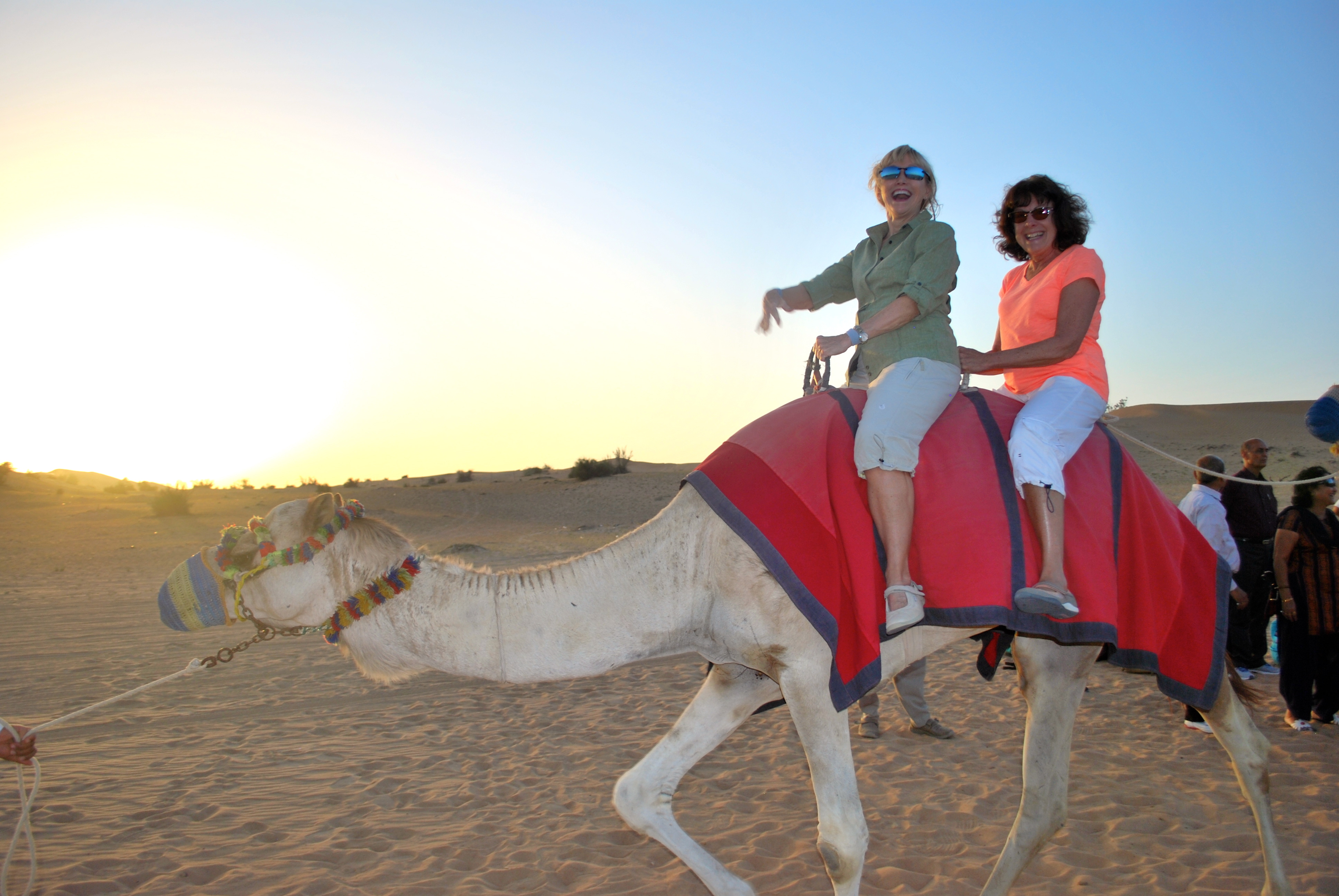 Two women riding a camel in the desert outside Dubai