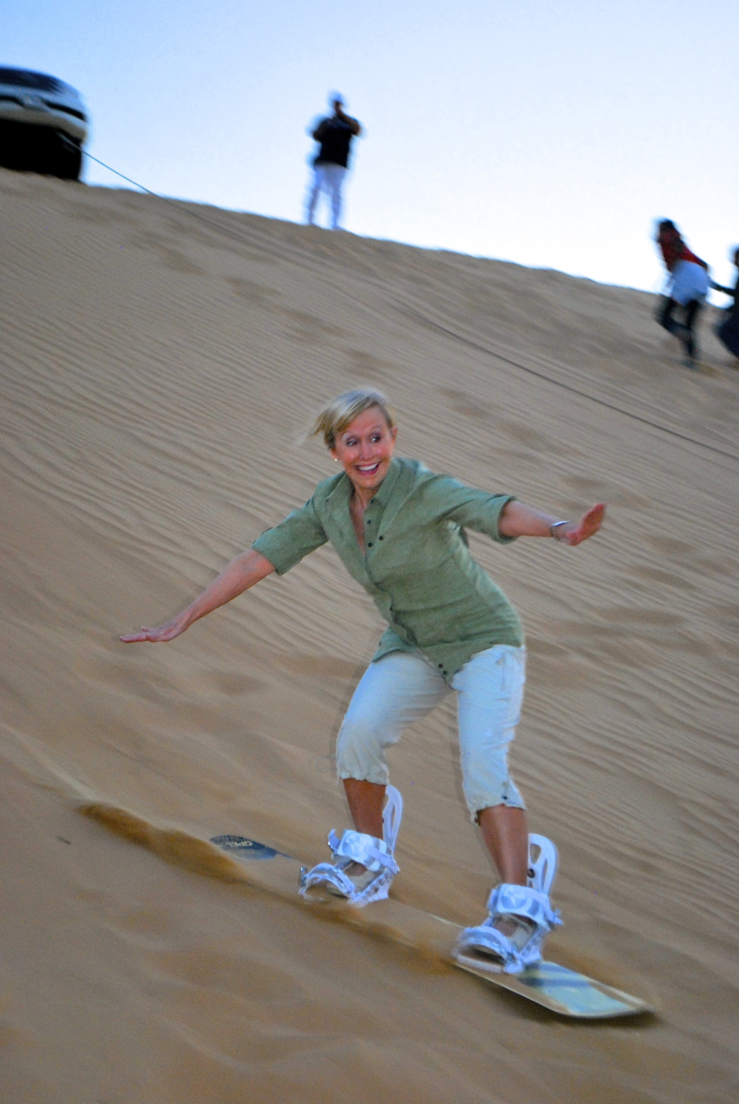 Blonde woman sand surfing on a dune in the desert