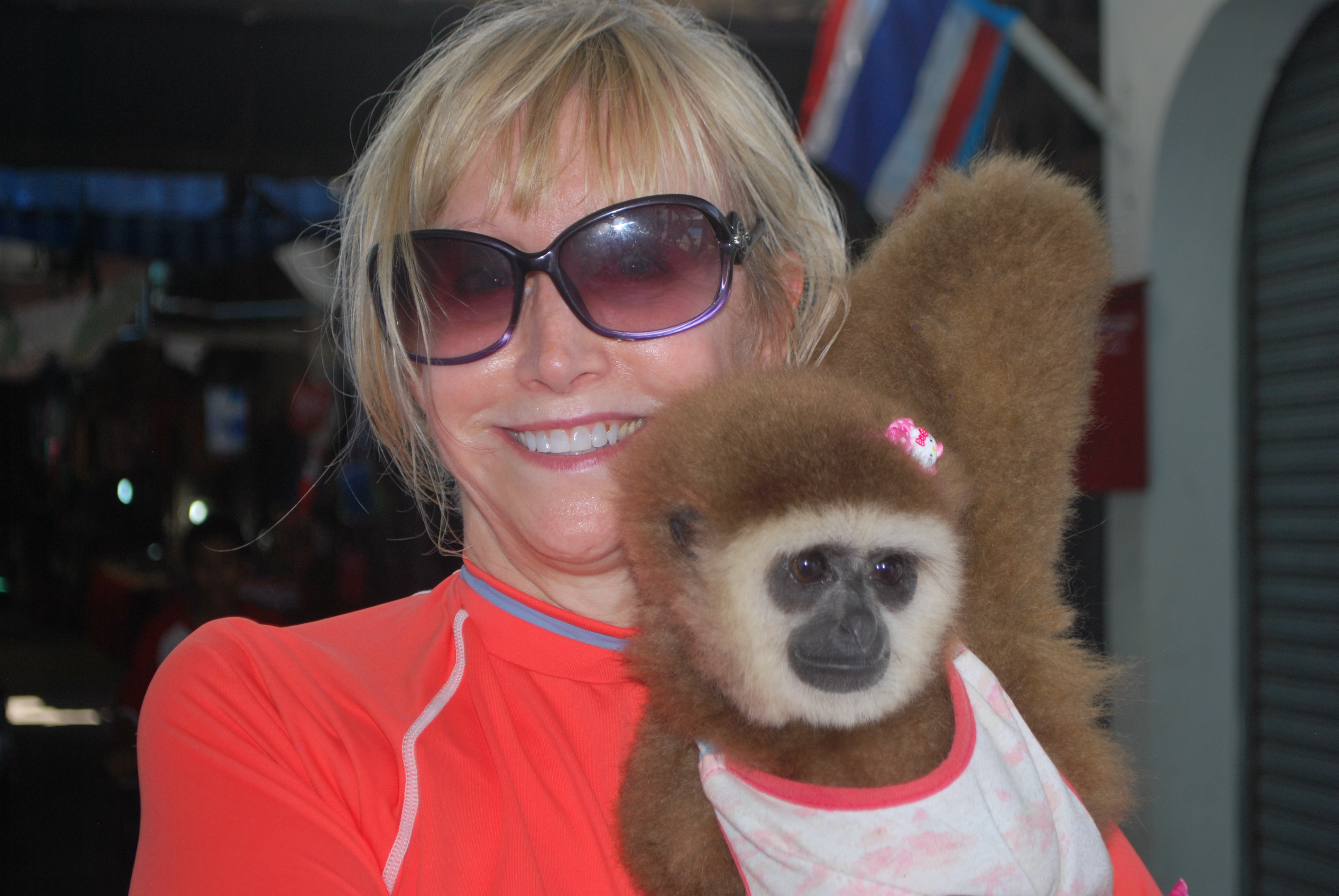 Blonde woman holding a gibbon in Thailand