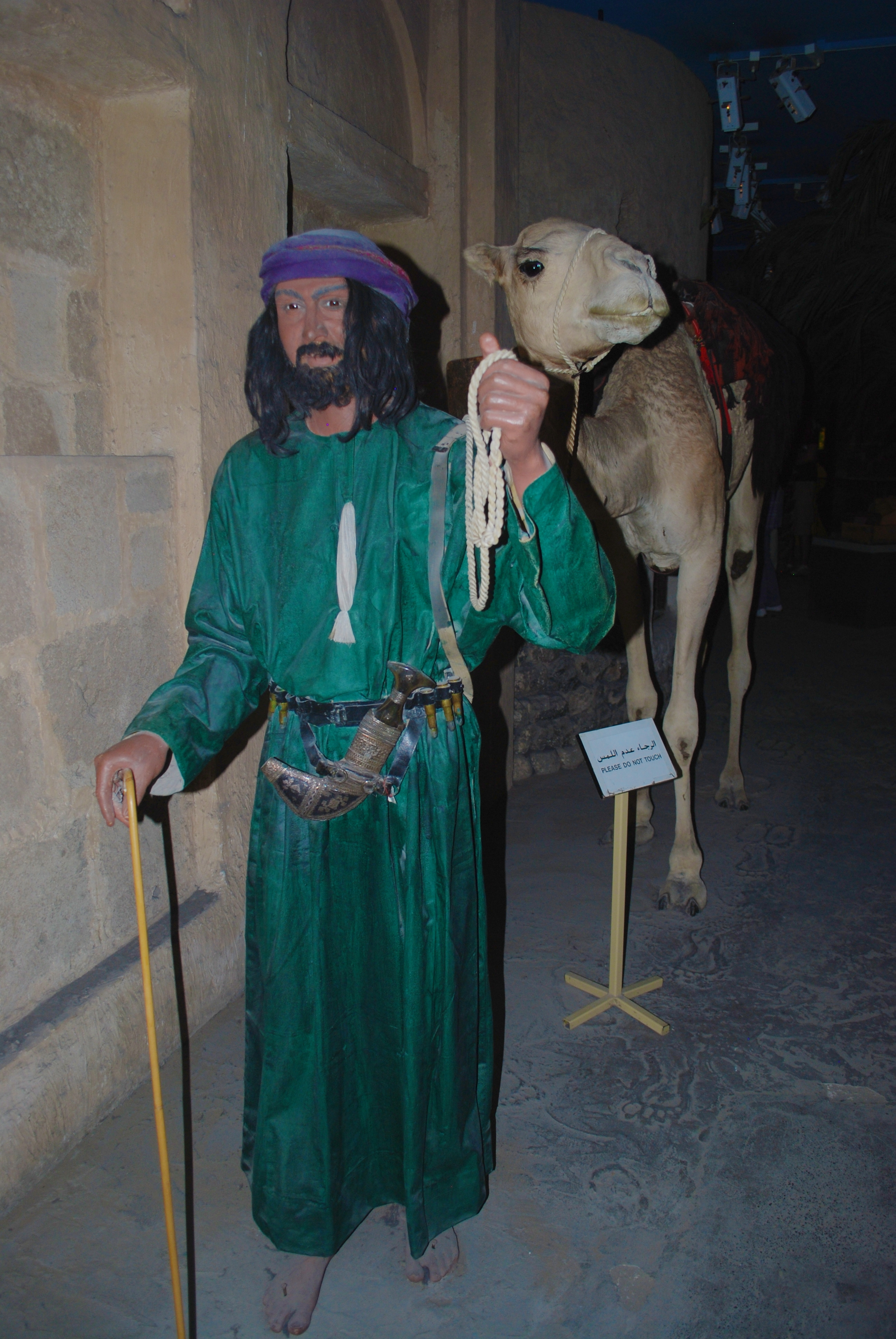 Man leading a camel out of a cave in the Dubai Museum