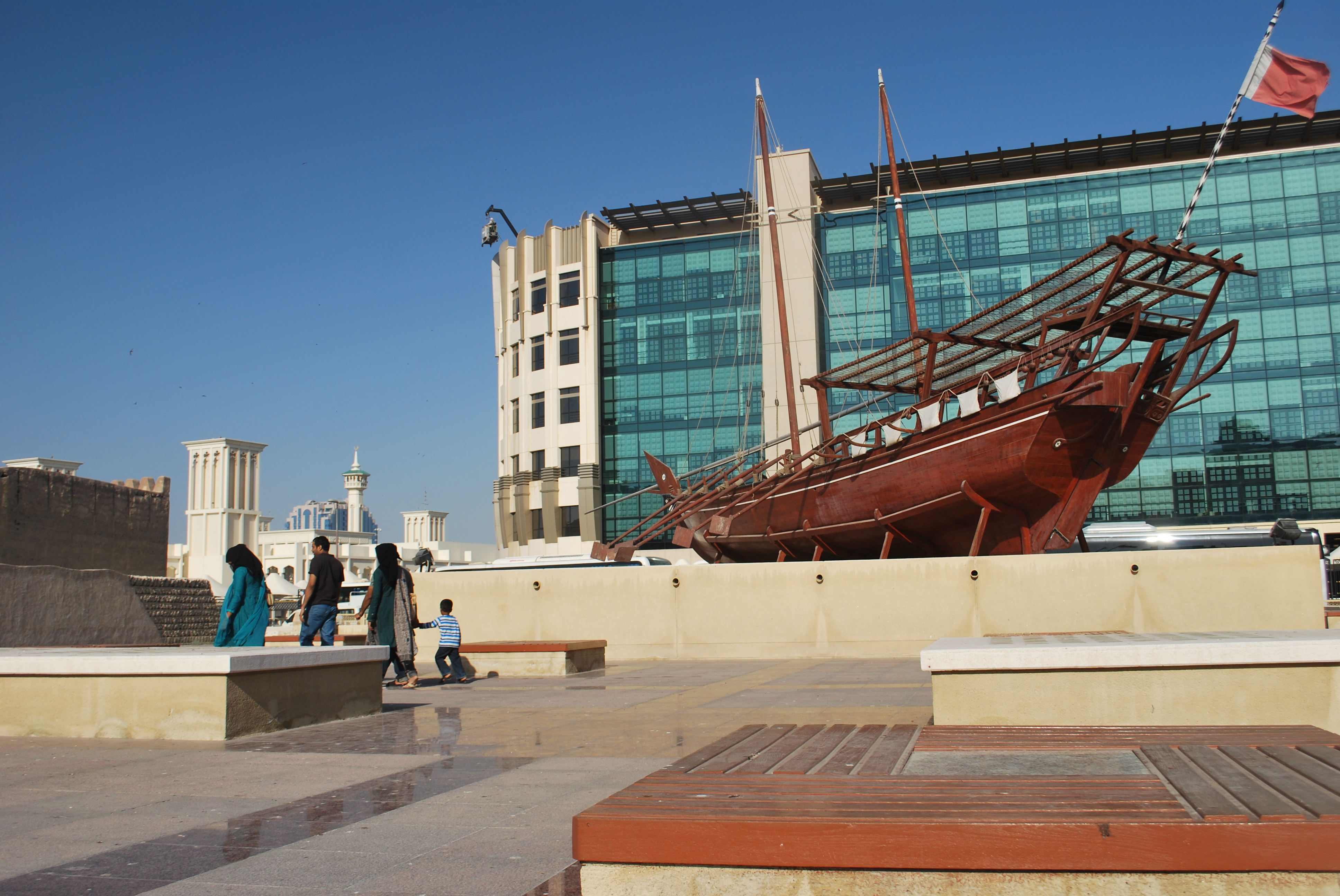 A dhow and a modern building juxtaposed in Dubai