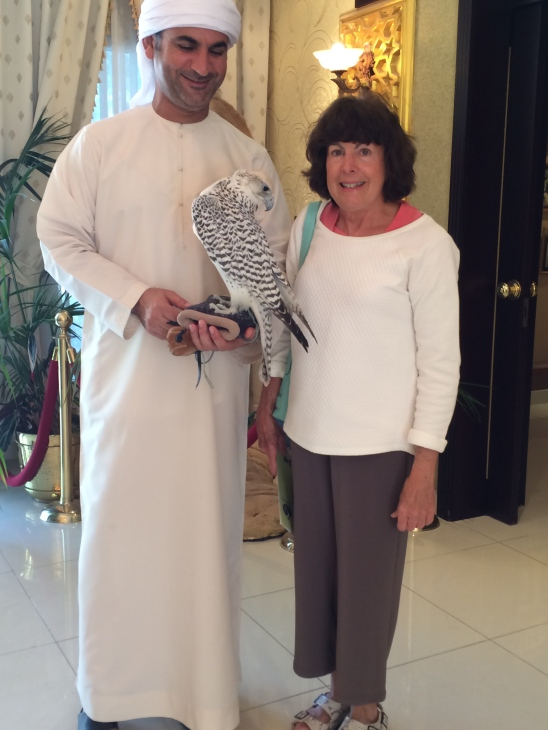Arab man holding a falcon with a woman standing beside him