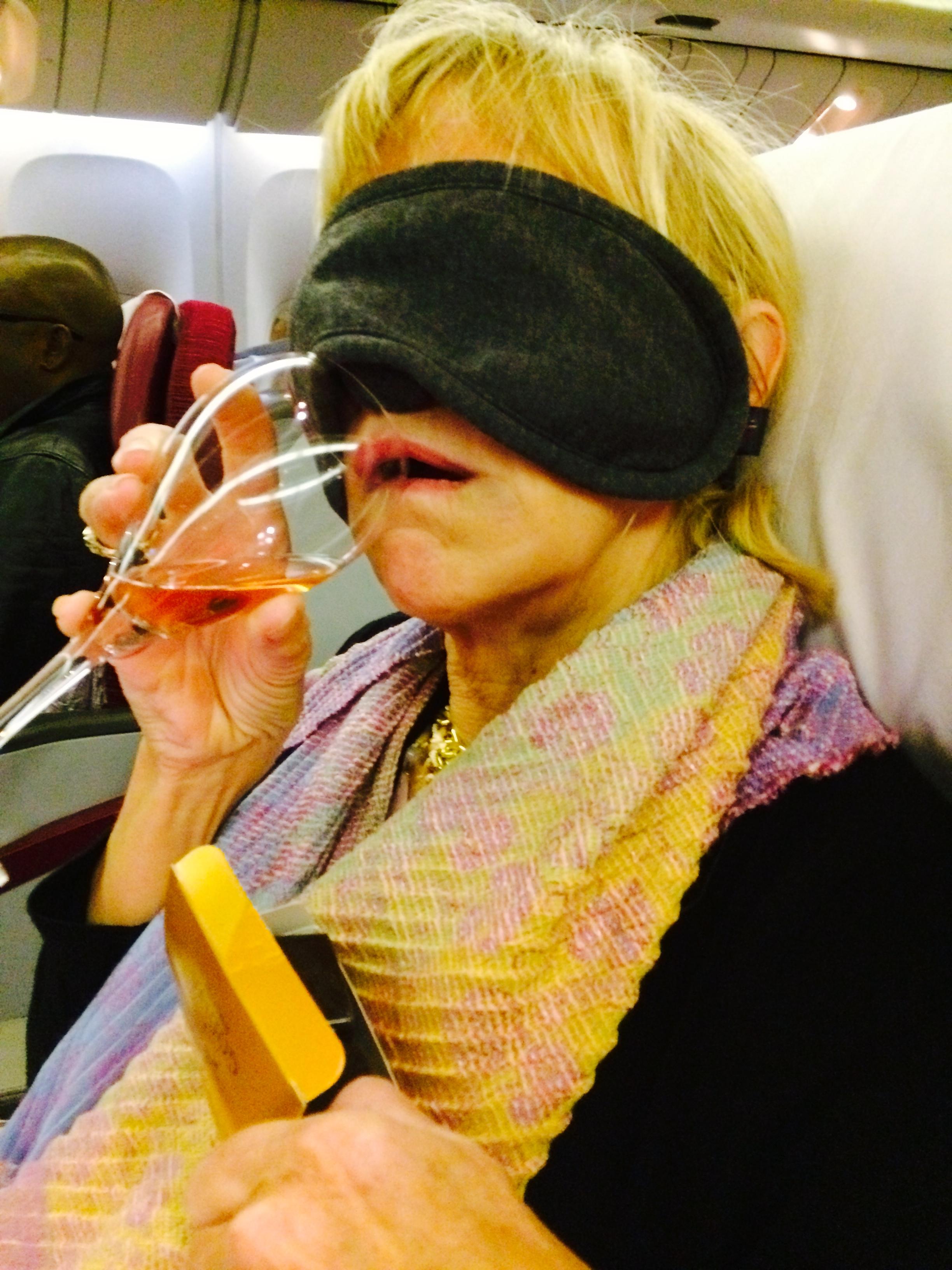Blonde woman in eye mask drinking wine