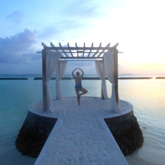 Woman doing yoga in a pagoda by the sea in the Maldives